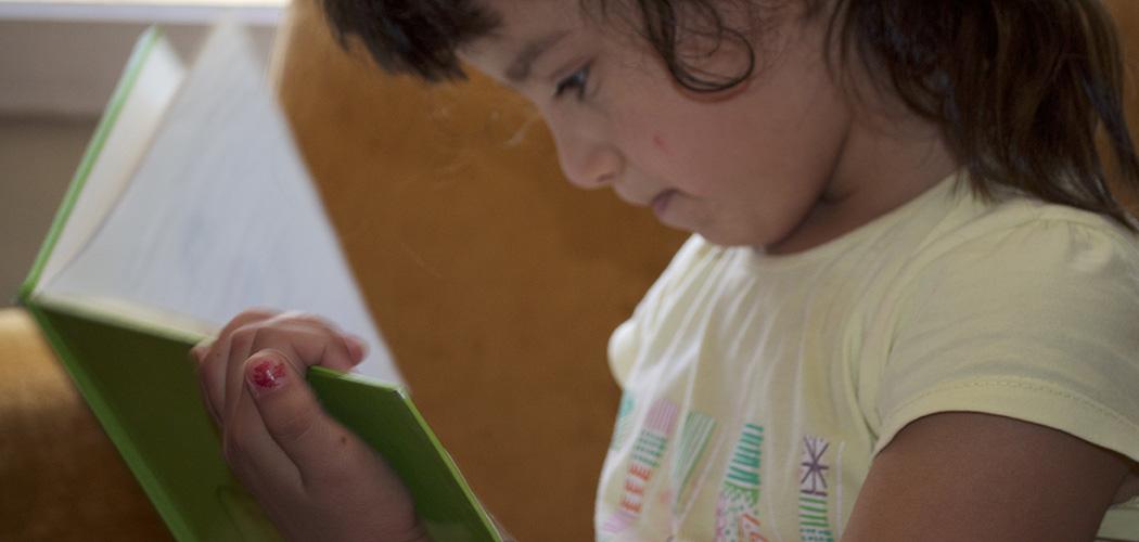 Bambina che legge un libro alla biblioteca della pace
