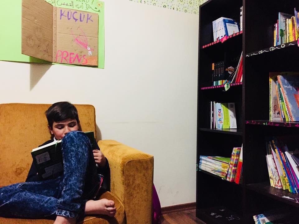 Bambino che legge alla biblioteca della pace